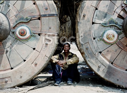 Kathmandu, Nepal - April 27, 2007: A daytime shot from a local man sitting between the wheels of a traditional ceremonial chariot in the streets of Kathmandu.