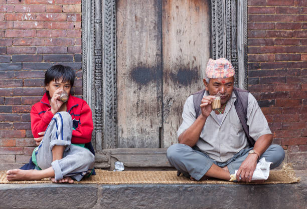 Nepalese father and son drinking Masala tea in Bhaktapur, Nepal stock photo