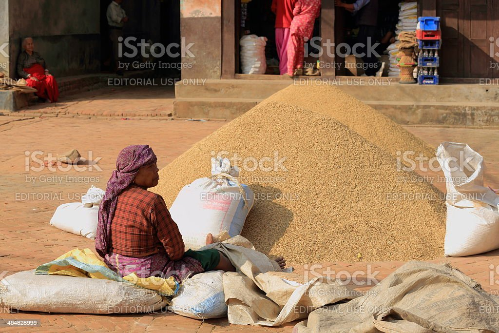 Nepalese woman filling in rice sacks. Panauti-Nepal. 1091