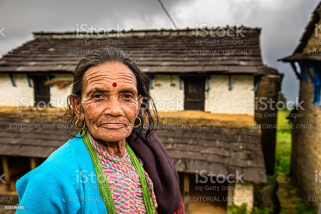 Nepalese woman in front of her farmhouse stock photo