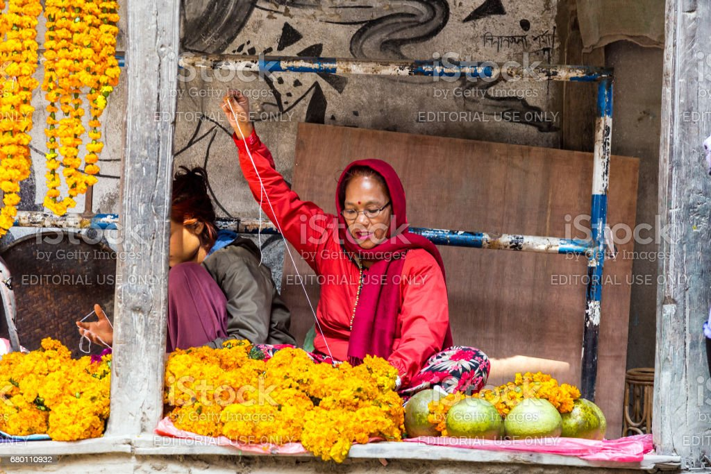 Nepalese Woman sewing traditional Holidays Flower Garlands stock photo