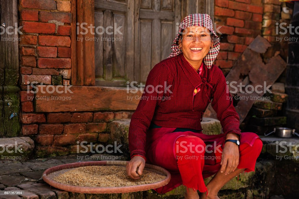 Nepalese woman sifting a rice, Bhaktapur stock photo