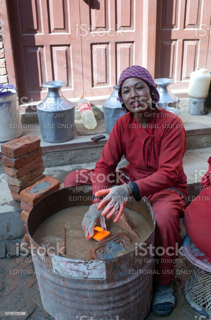 Nepalese woman working hard in building in Bhaktapur, Nepal stock photo