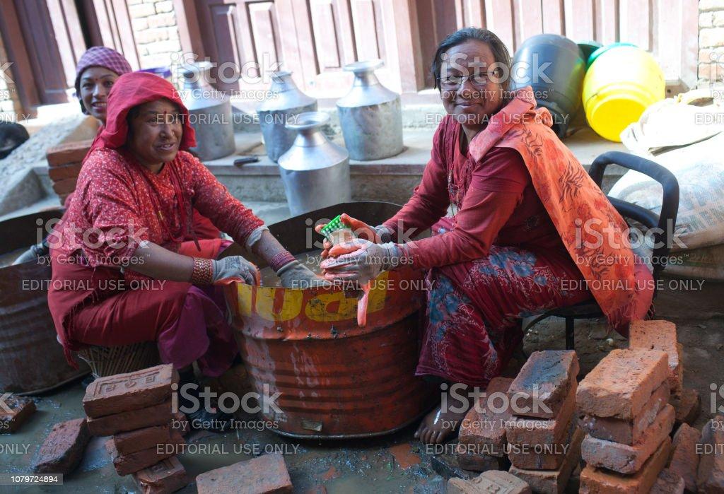 Nepalese women working hard in building in Bhaktapur, Nepal stock photo