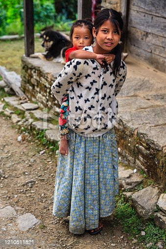 Nepali girl carrying her little sister, village in Annapurna Conservation Area