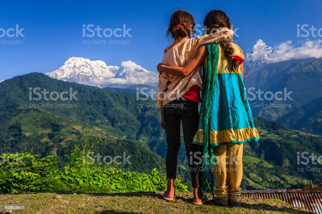 Nepali little girls looking at Annapurna South stock photo
