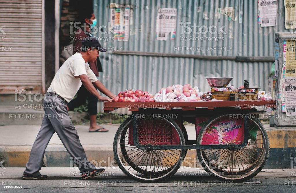 Nepali Man Pushing Cart Selling Fruit Across Thamel Street stock photo