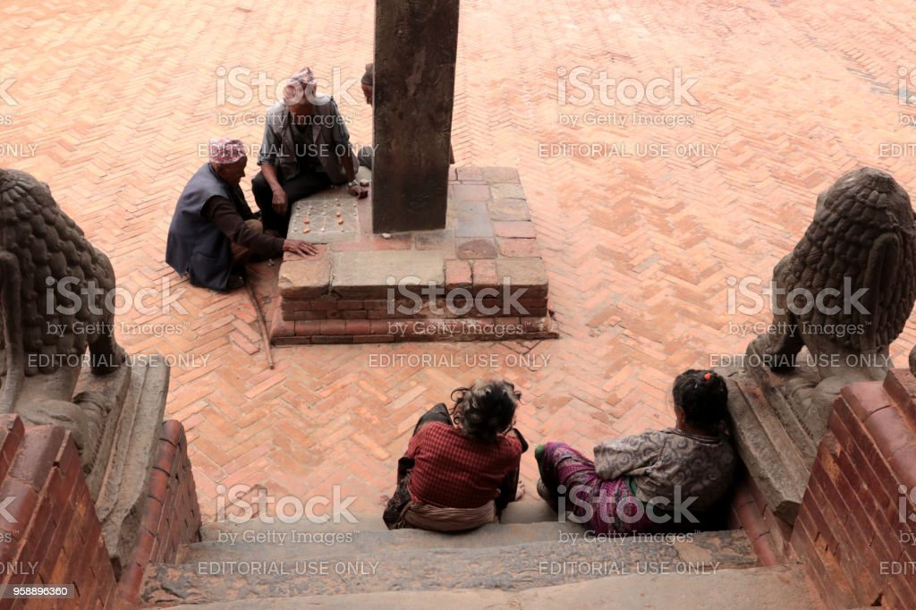 Nepali men playing traditional Nepal game using stones and a playfield signed by chalk stock photo
