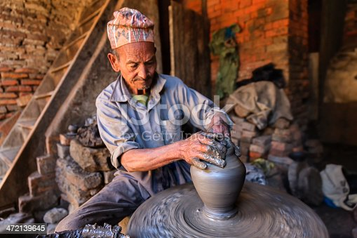 Nepalese potter working in his workshop on pottery square in Bhaktapur. Bhaktapur is an ancient town in the Kathmandu Valley and is listed as a World Heritage Site by UNESCO for its rich culture, temples, and wood, metal and stone artwork.