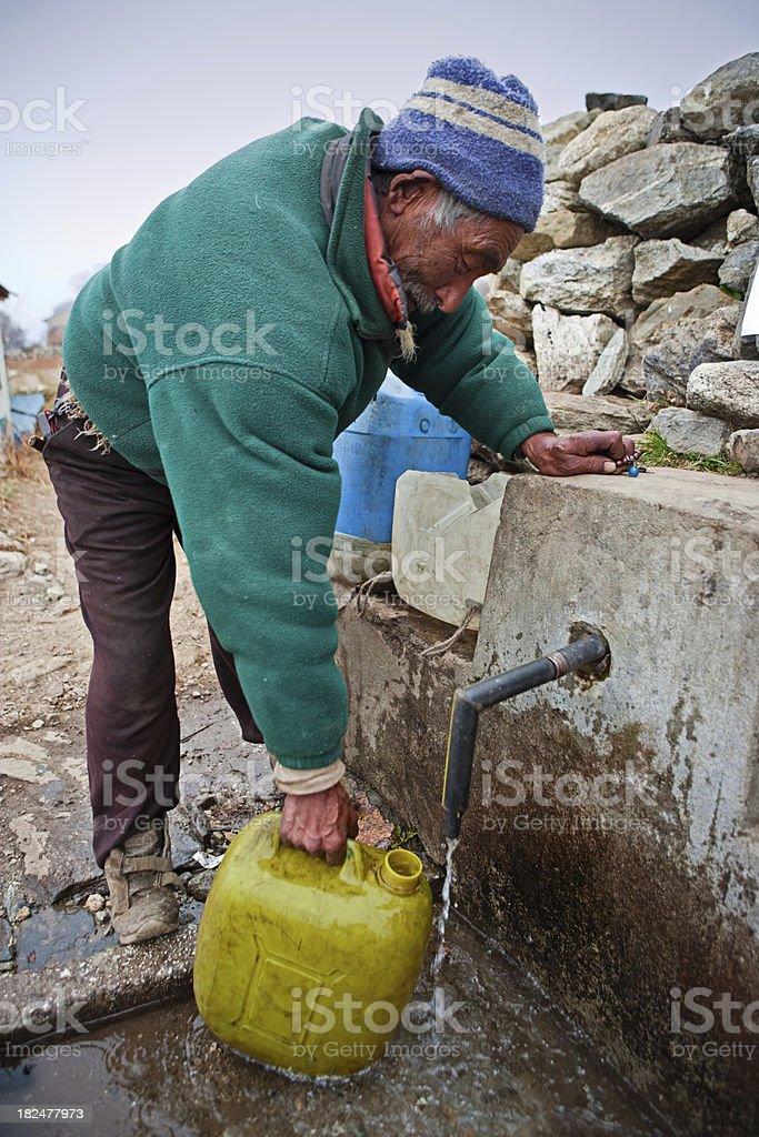 Nepali sherpa getting water from village fountain stock photo