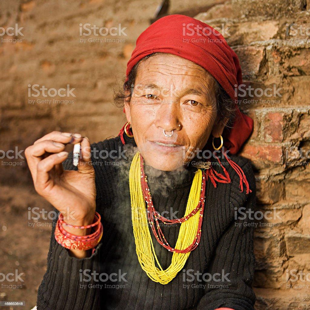 Nepali woman smoking cigarette. Bhaktapur. stock photo