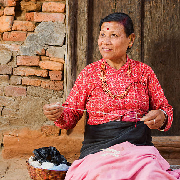 Nepali woman spinning the wool stock photo