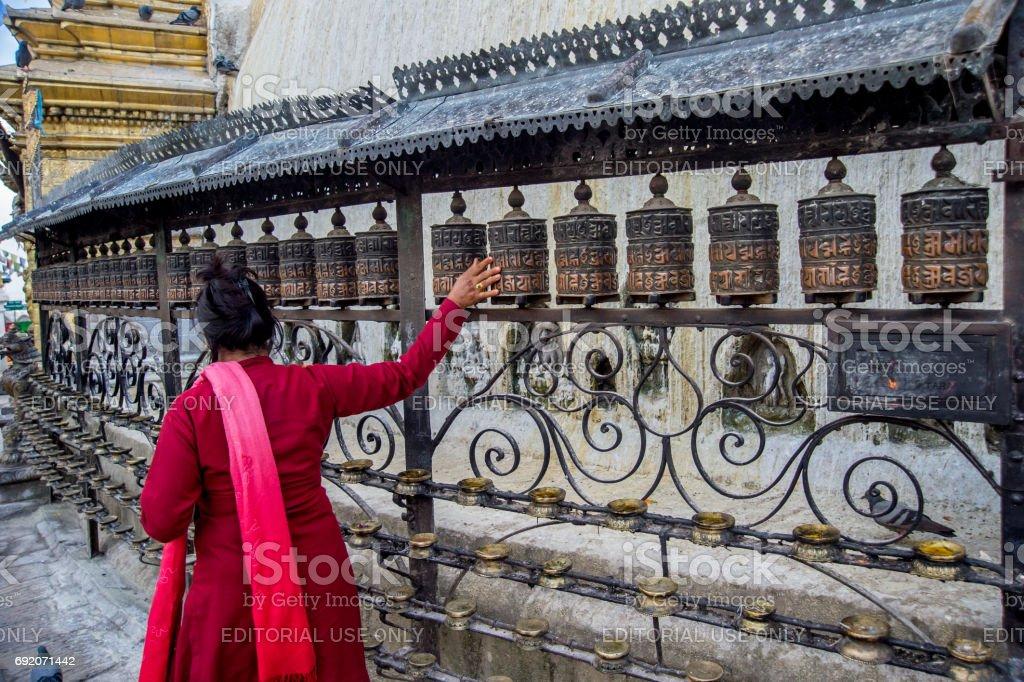 Nepali woman turning prayer wheels stock photo