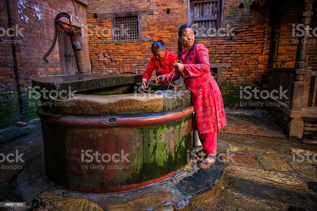 Nepali women getting water from the well in Bhaktapur stock photo