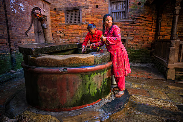 Nepali women getting water from the well in Bhaktapur stock photo