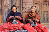 Two Nepali women kniting a wool hat in front of the house. Bhaktapur in Kathmandu valley. Nepal.http://bhphoto.pl/IS/nepal_380.jpg