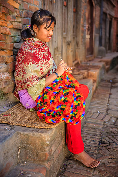 Nepali young woman  kniting a wool scarf in Bhaktapur. stock photo