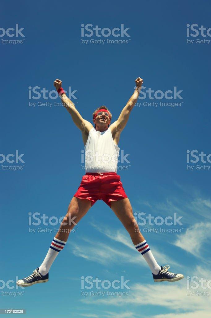 Nerd Athlete Does a Spreadeagle Jump in Blue Sky stock photo