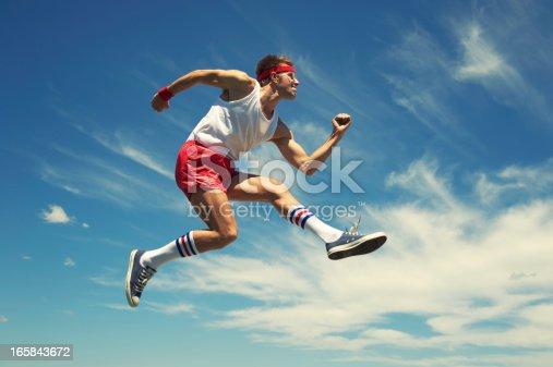 Nerd athlete in headband and 70s socks leaps against blue sky