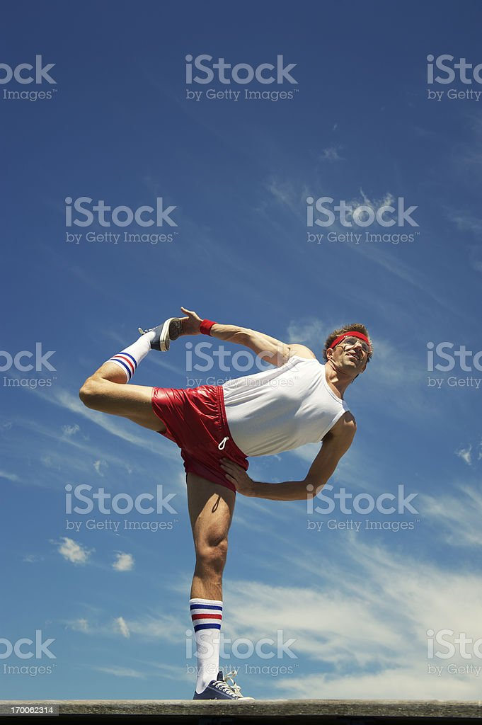 Nerd Athlete Stretches Against Blue Sky stock photo