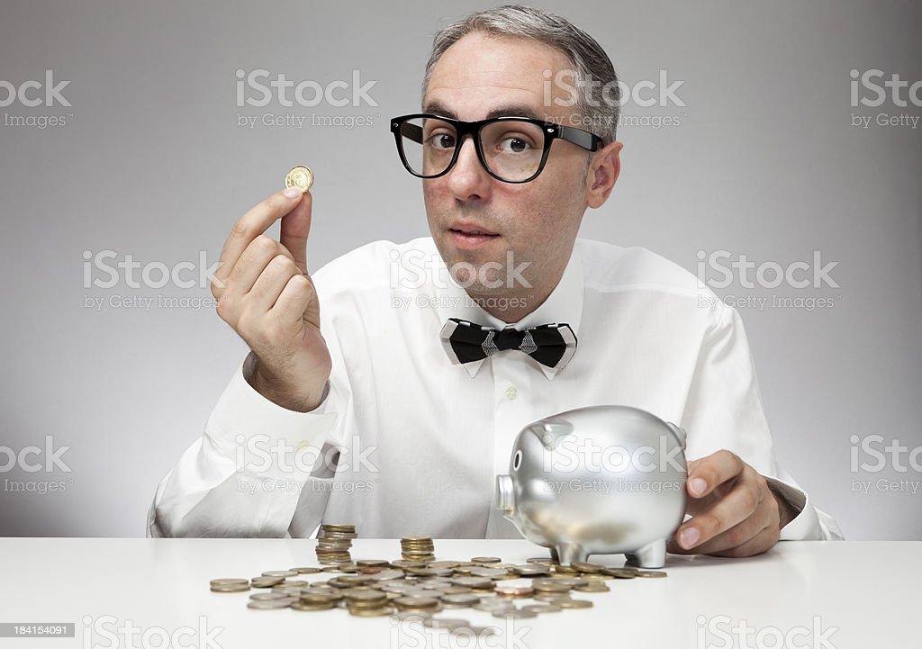 Nerd businessman saving money in a piggy bank royalty-free stock photo