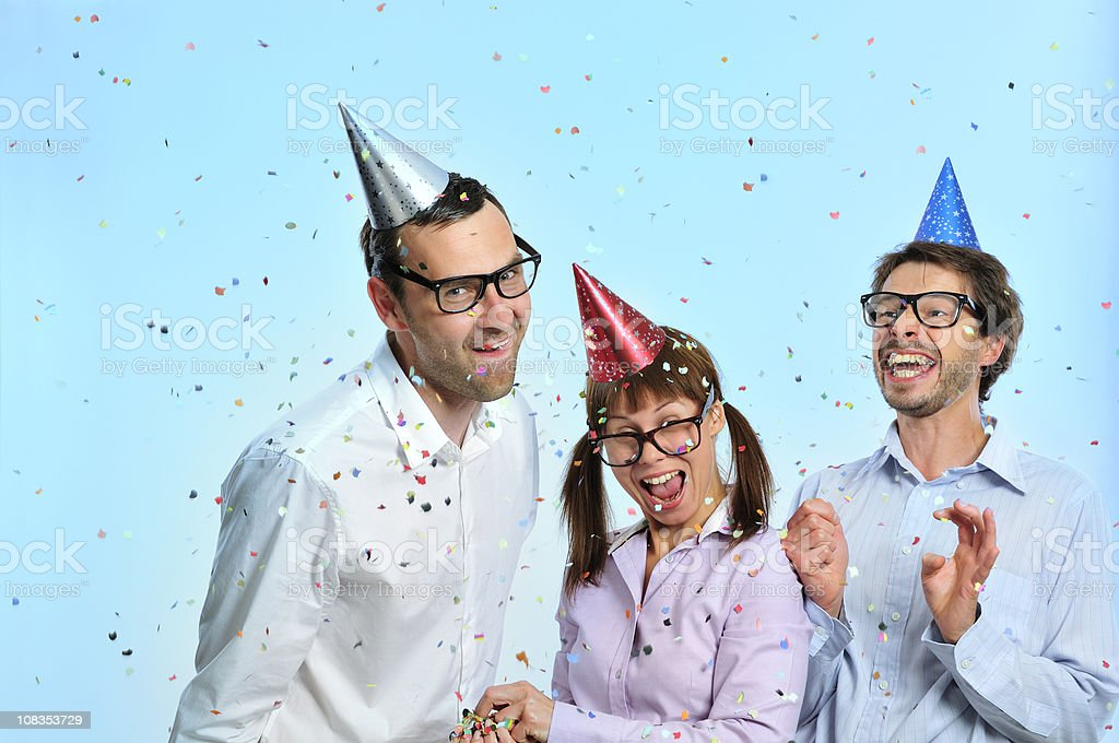 Nerd friends with party hats on head, confetti, toothy smiling royalty-free stock photo