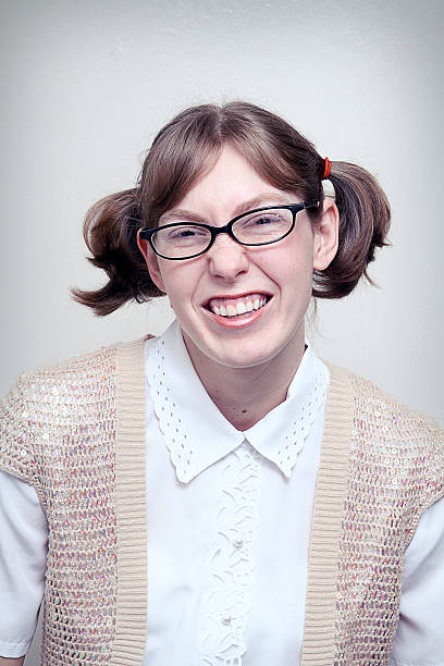 Nerd Girl Highschool Picture A nerdy young woman poses for a portrait shot.  Vertical with copy space. nerd hairstyles for girls stock pictures, royalty-free photos & images
