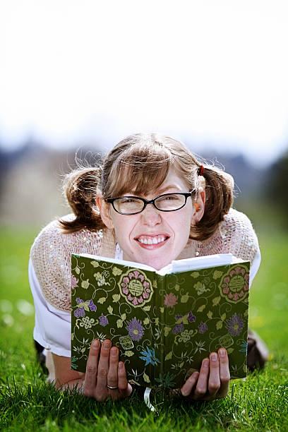 uncool mädchen studieren einem lehrbuch - pailletten shirt stock-fotos und bilder