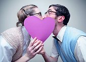 istock Nerd Guy and Girl in Love Kissing Behind A Heart 156278033