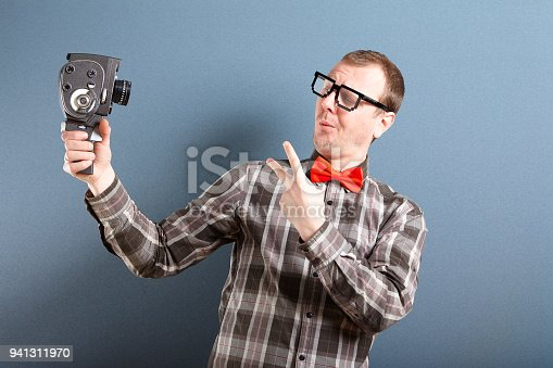 Nerd guy wearing glasses holding holding old video camera and taking selfie. Behind him is blue background