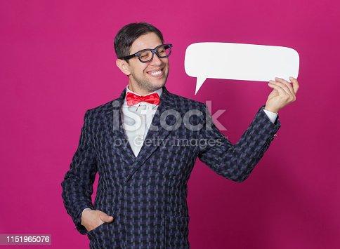 Nerd man holding speech bubble over pink background