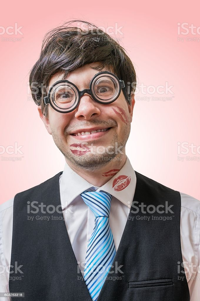 Nerd or geek was kissed by woman. Many lipstick kisses. stock photo