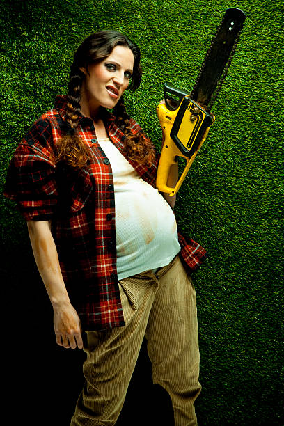 Nerd embarazada leñador sosteniendo una sierra de cadena - foto de stock