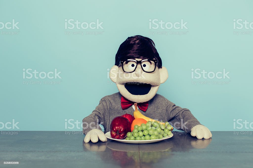 Nerd Puppet with Glasses Loves Eating Fruit stock photo