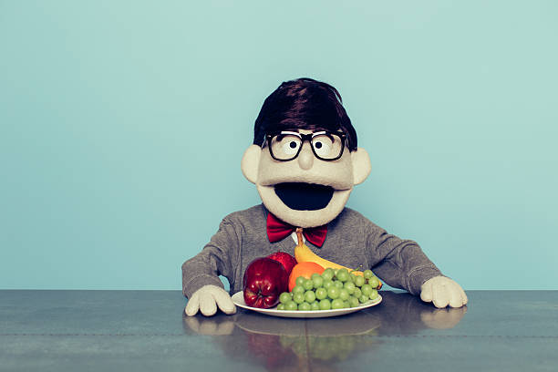 Nerd Puppet with Glasses Loves Eating Fruit A nerd puppet with glasses is excited to eat his fruit. He is sitting at a table with an apple, banana, grapes and an orange and has an excited expression on his face.  ventriloquist's dummy stock pictures, royalty-free photos & images