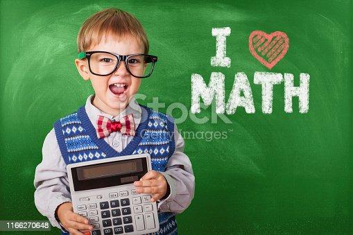 Nerd Schoolboy Wearing Glasses Holding Calculator In Front Chalkboard, Back To School