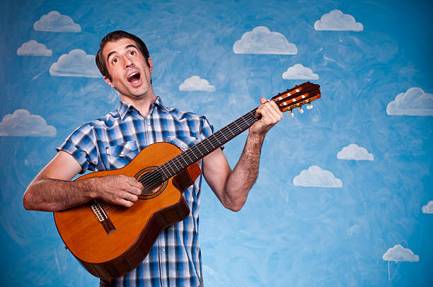 Nerd Serenading With Guitar Happy nerd Serenading with his guitar. The background is hand painted and the image is shot in the studio. serenading stock pictures, royalty-free photos & images