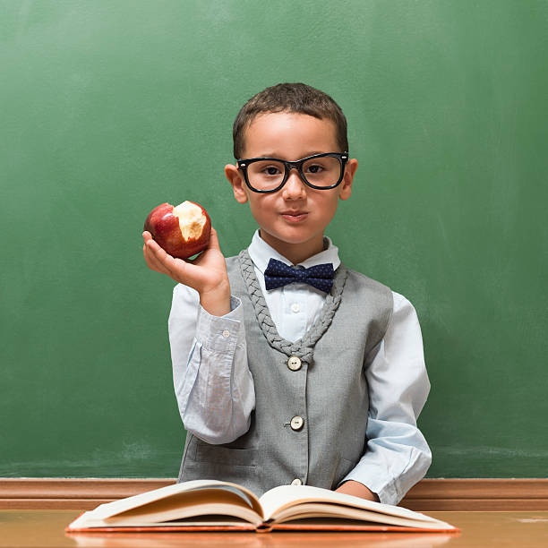 nerd student eating apple in classroom - nerd boy eating stock photos and pictures