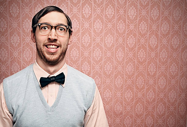Nerd Student With Retro Glasses and Pink Wallpaper Nerdy IT young man makes a goofy face with pink copy space background.  Horizontal. ugliness stock pictures, royalty-free photos & images
