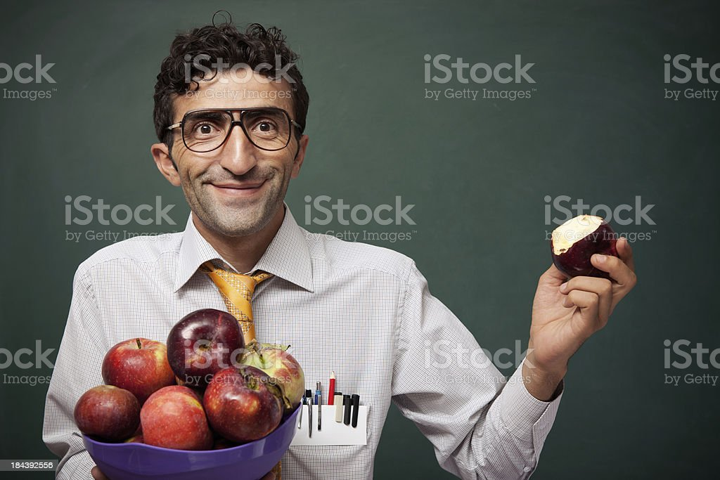 Nerd teacher in classroom with basket of apples royalty-free stock photo