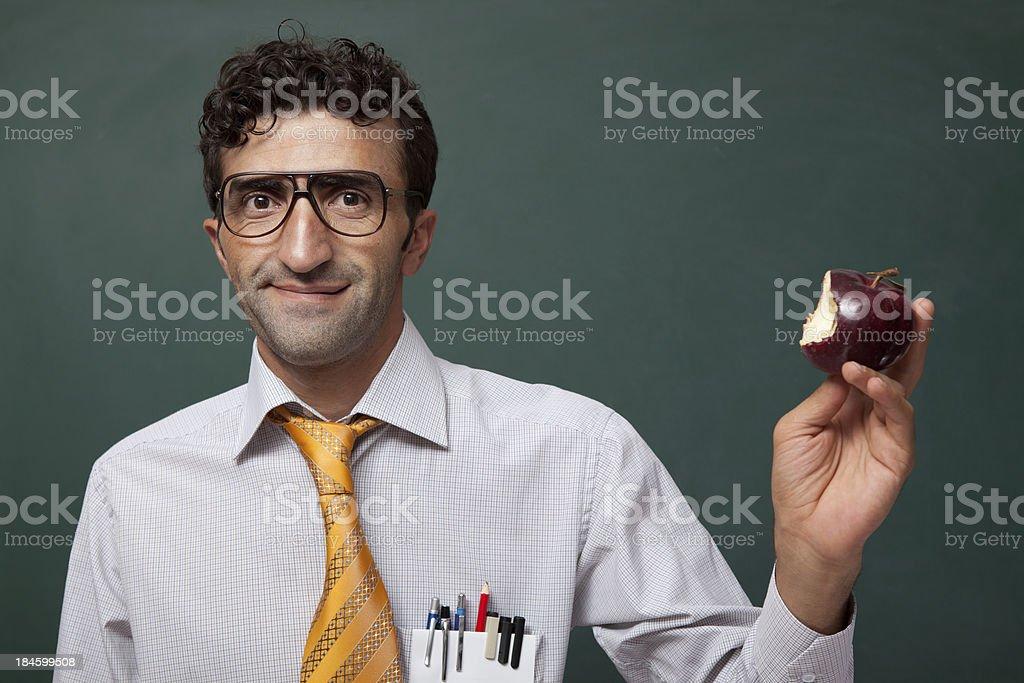 Nerd teacher in classroom with bitten apple
