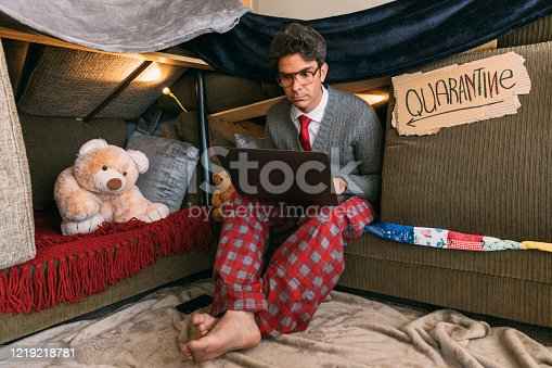 A hip nerd, who is under a shelter in place order, is teleworking from home. He is dressed in shirt and tie on the top, pajamas on the bottom while he works on his laptop from Quarantine.
