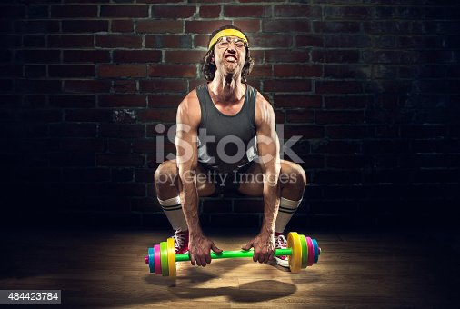 A man in retro active wear and nerdy glasses struggles to lift a colorful toy weight lifting set.  Here he attempts a deadlift or squat snatch.  Cross training workout.  Horizontal image with copy space.