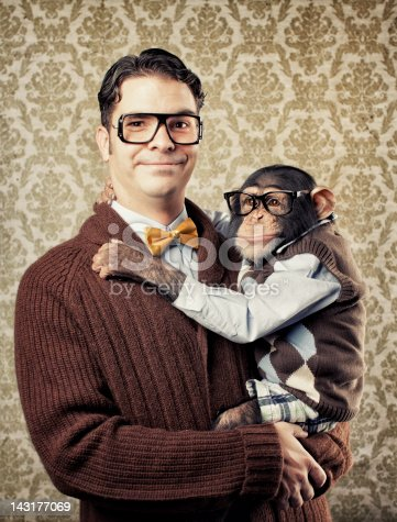 A vintage nerd and professor poses with a chimp.