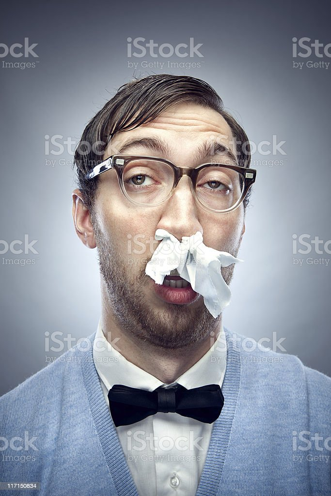 Nerd with a Cold and Tissue in Nose stock photo