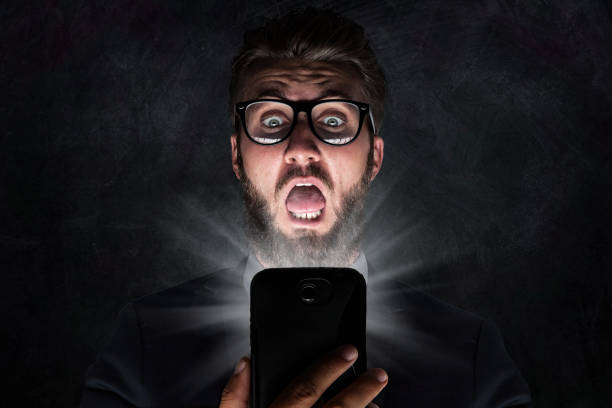 Nerd with glasses is shocked after reading a sms stock photo