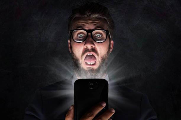 戴眼鏡的神經在看了短信後感到震驚 - 吃驚 個照片及圖片檔