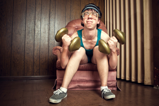 A goofy, nerdy teenager with tank top, corduroy shorts, sweatband, and glasses, strains to lift his dumbbell weights in a vintage basement, complete with linoleum and wood paneling on  the walls.  He sits in a plush pink armchair. Horizontal with copy space.