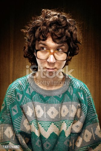 A nervous nerdy teenager with bad 1980s sweater and glasses, looks shy.  Wood paneling in the background.  Vertical with copy space.