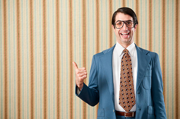 Nerdy Businessman In Retro Suit Nerdy businessman wearing a blue retro suit giving a thumbs up. The wall has a brown beadboard wainscoting and a striped wallpaper.. nerd stock pictures, royalty-free photos & images
